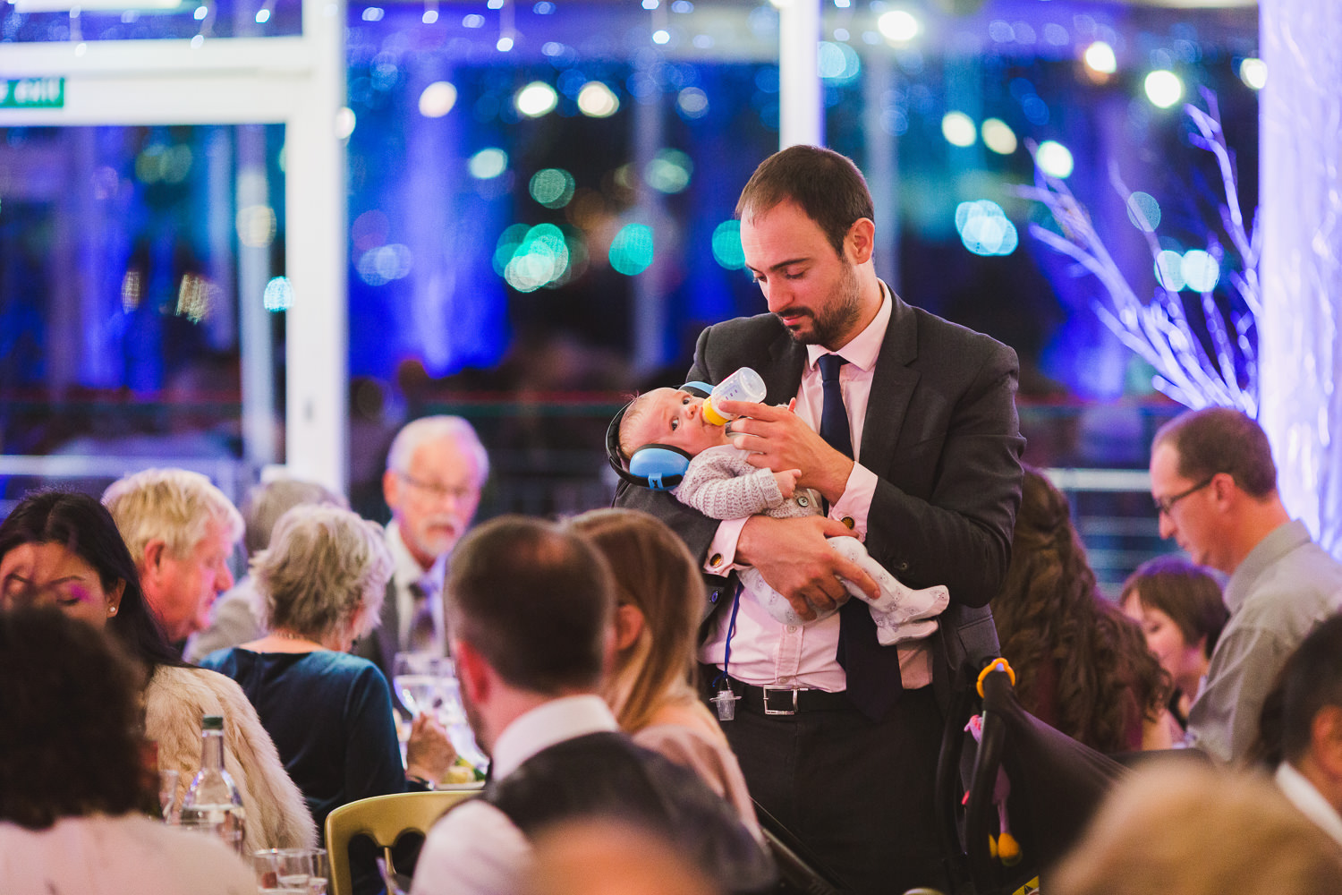 man feeding baby with headphones at loud wedding reception